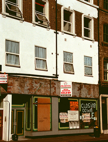 "The ground, first, and second floors of a terraced double-width shop.  One of the ground-floor windows is boarded over, and the others have flyposters on.  ""Closing down sale"" has been spraypainted in one window, partially obscured by a flyposter. Windows on the upper floors are open, indicating those floors are still inhabited."