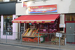 "A terraced shopfront with vegetables including yams, peppers, chillies, and sacks of onions displayed at the front.  A sign above reads ""Kandil / African Caribbean Food Land / Quality Meat & Fresh Fish"".  A red canopy stretches over the vegetables, with ""Fresh Fish / Beef / Lamb / Goat / Mutten [sic] / Grocery"" printed on it."