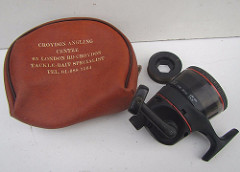 "A brown leather bag with ""Croydon Angling Centre / 65 London Rd Croydon / Tackle-Bait Specialist / Tel. 01-688 7564"" printed on it in gold.  Next to it is a black fishing reel with red bands, around the same size as the bag."