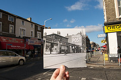 A vintage black-and-white photo held up in front of the same scene today.  The older shopfronts include Victor Value and Egleton Bros Ltd, while the modern ones include MBM Fresh Fish, Perfect Chicken, and Chat Patta.