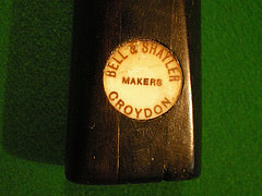 "The end of a billiards cue with a circular imprint reading ""Bell & Shayler / Makers / Croydon""."