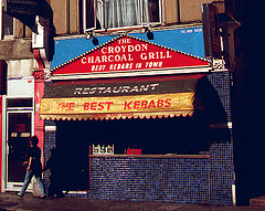 "A terraced shopfront with a person walking past.  The front is covered with small, square, blue and blue-black tiles.  A blue and red sign above reads ""The Croydon Charcoal Grill / Best Kebabs In Town""."
