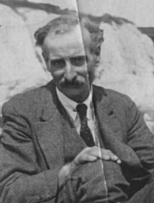 A black-and-white photo of a white man with receding wavy hair and a relatively substantial moustache.  He is wearing a suit with waistcoat and a tie, and appears to be sitting on the ground with a hand on one knee.  In the background is something that could be a rock or cliff.