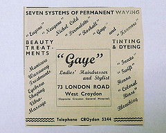 "A black-and-white newspaper advert reading: ""Seven systems of permananent waving / 'Eugene' 'Neugene' Nichol Cold 'Permalette' 'Roshall' 'Gaye' and 'Kenmore' / Beauty treatments / Tinting & dyeing / Manicure / Waxaway Treatments / Eyebrow Shaping / Vibra-Massage / 'Inecta' 'Swift' Henna 'Coloral Rinse' Bleaching / 'Gaye' Ladies' Hairdresser and Stylist / 73 London Road / West Croydon / (Opposite Croydon General Hospital) / Telephone CROydon 5244""."
