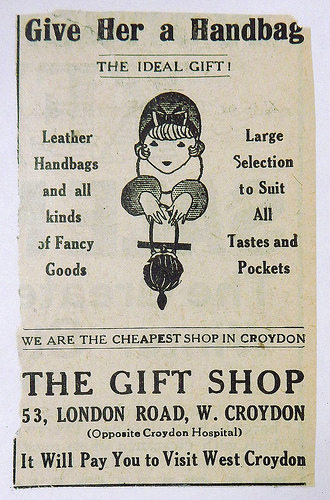"A black-and-white newspaper advert with a drawing of a women holding a fancy handbag and the text: ""Give Her a Handbag / The Ideal Gift! / Leather Handbags and all kinds of Fancy Goods / Large Selection to Suit All Tastes and Pockets / We are the cheapest shop in Croydon / The Gift Shop / 53, London Road, W. Croydon / (Opposite Croydon Hospital) / It Will Pay You to Visit West Croydon"""