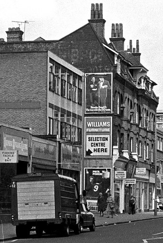 A black-and-white photo with an oblique view onto a 1960s office block next to a 1890s four-storey terrace.  Three advertisement posters are visible on the side wall of the terrace.