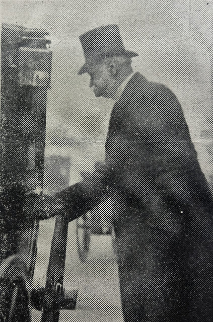 A black-and-white photo of a white man in a top hat and dark coat, seen sideways on, with his hand on the door of a carriage. He appears not to have noticed the photographer.
