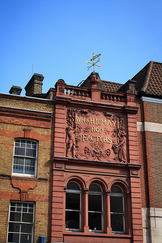 "The upper floors of a narrow terraced building, seen in full sunlight.  The building is terracotta in colour, and has a sign on the top floor reading ""WH & H LeMay Hop Factors"" with an elaborately moulded surround."