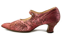 A salmon-pink brocade shoe with a medium-high heel and a slightly pointed tow.