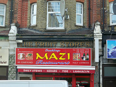 "An old sign reading ""The Fruit Stores"", visible above a newer sign reading ""Mazi""."