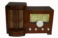 An old-fashioned radio with a dark brown varnished case, a speaker to the left, and a dial to the right.