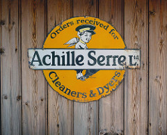 "A circular yellow/orange sign with a drawing of a person with pointed ears, wings, and a flat uniform cap.  A white bar runs across the centre of the sign with the words ""Achille Serre Ltd."", supplemented by curved wording on the circular part of the sign: ""Orders received for [white bar here] Cleaners & Dyers""."