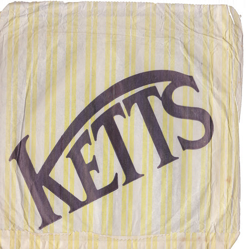 "A square paper bag with yellow and white stripes and a large ""Ketts"" logo running diagonally upwards."