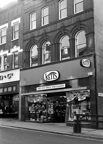 "A black-and-white photo of an end-of-terrace shopfront. Signage above the ground-floor shop reads ""Ketts / The Cut Price Specialists"".  Televisions, washing machines, and other electrical goods are visible in the window."