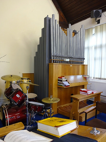A colour photo of a small pipe organ in the corner of a room next to a drumkit.  A yellow bible is visible on a lectern in the foreground.