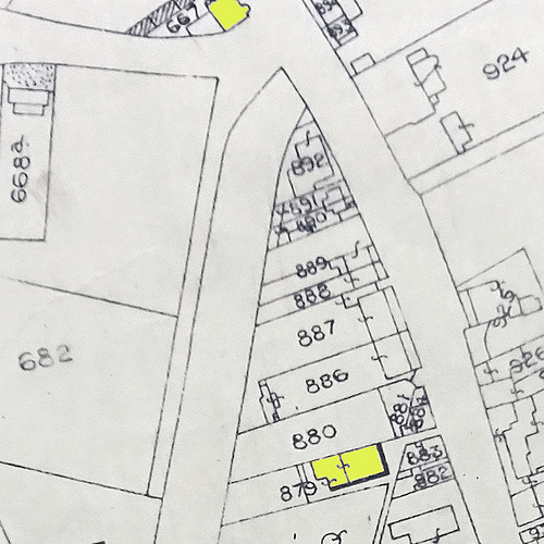 A map showing numbered plots; highlighted in yellow at the bottom is a building on plot 879.  What appears to be a narrow path leads slantwise from this between buildings to a wide road.