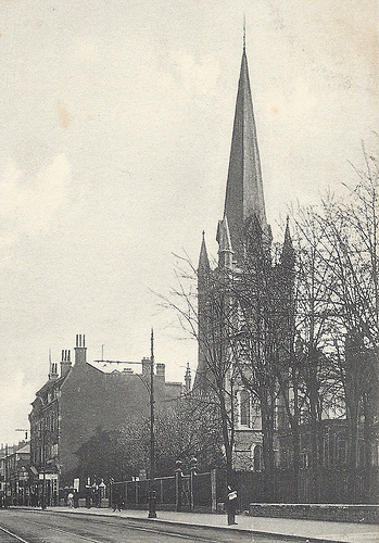 A black-and-white photo of a church with a spire towering over the other buildings around it.  Leafless trees stand in front, and tram tracks are just visible along the road.