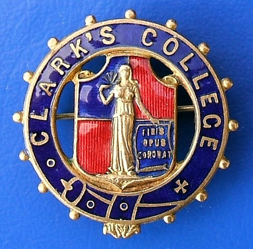 "A round enamel badge in blue and red.  ""Clark's College"" is embossed around the circumference, and a figure holding a sign reading ""Finis Opus Coronat"" is in the centre."