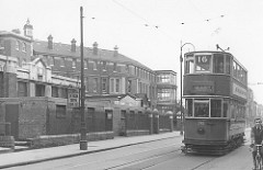 "Black-and-white photo of an old-fashioned double-decker tram running along a road next to a tall, bulky building.  A sign on a post reads ""Hospital / Please Drive Quietly"".  A cyclist is just visible in the foreground on the other side of the tram."
