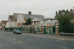 A light grey stone building behind green railings, viewed from the other side of a wide but quiet road.  All of the windows are boarded up with what looks like chipboard.
