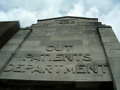 "A stone façade with ""1926"" embossed at the top and ""Out Patients Department"" below."