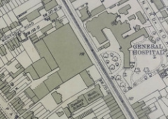 A map showing buildings marked with shading on either side of a road running diagonally with tramlines marked on it.