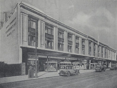 A black-and-white image of a long three-storey building with a columnar look on the upper two floors and a suggestion of individual glazed shopfronts on the ground floor.