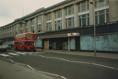 The same long three-storey building as above, but with the windows of the ground floor whitewashed over.  A Routemaster bus on route 109 is just passing over the zebra crossing at the front of the building.