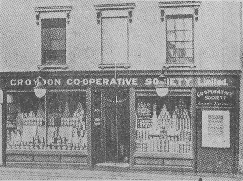 "A black-and-white photo of a small terraced shopfront, with display windows on either side of a recessed central door and the name ""Croydon Co‑operative Society Limited"" above."