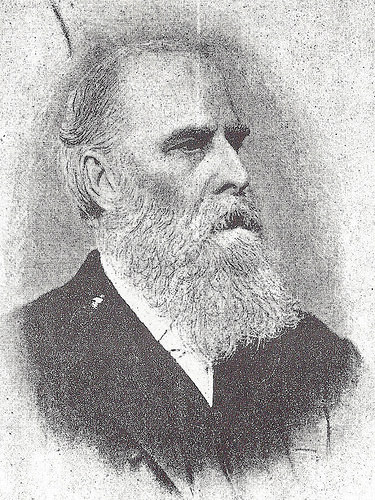 A black-and-white photograph of a white man with a receding hairline, a prominent browline, and a full white beard and moustache.  He is wearing a white shirt and dark jacket, and looking somewhat stern.