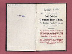 "A small opened book with the printed name and address of the South Suburban Co‑operative Society Limited at 99 London Road, Croydon.  Below, it states: ""The payments must be made in full punctually as they become due, and members are requested to see that they obtain a dividend check when each payment is made.  Upon completion of payments please forward this book to Office, London Road, Croydon, for official cancellation.""  Two dates have been stamped opposite: ""5 Oct 1949"" and ""6 Sep 1951""."
