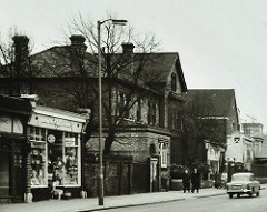 A black-and-white photograph showing a 2–3-storey brick house with peaked roofs and protruding extensions.  A few people are on the pavement outside, and an old-fashioned car is in the road.  A small terrace of shops begins to the left.