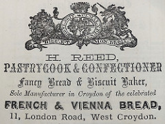 "A black-and-white printed advert with a rather squashed version of the United Kingdom royal coat of arms at the top and wording below in six different fonts: ""H. Reed, Pastrycook & Confectioner / Fancy Bread & Biscuit Baker, Sole Manufacturer in Croydon of the celebrated French & Vienna Bread, 11, London Road, West Croydon."""