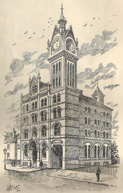 "A monochrome drawing of a four-storey building with a clocktower reaching further up from one corner.  A weathervane can just be seen on another tower in the opposite corner, behind.  Two or three steps lead up to a grand arched entrance on the left, and on the right below the clocktower is a wide goods entrance with the words ""J Thrift & Sons"" above."