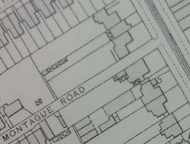 "A small section of a printed map.  A road with tramlines runs diagonally along the top right corner, and a side road off from this is labelled ""Montague Road"".  Just to the north of Montague Road there are three houses adjoining each other, set back slightly from the main road."