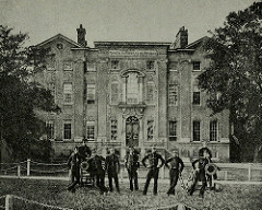 A black-and-white photograph of a three-storey building with a grand arched entrance.  Trees are to either side.  Nine people are posing in front of the building, all fairly tall and thin, and all dressed in uniform; several of them are leaning on the small cannons drawn up on each side of the groups.