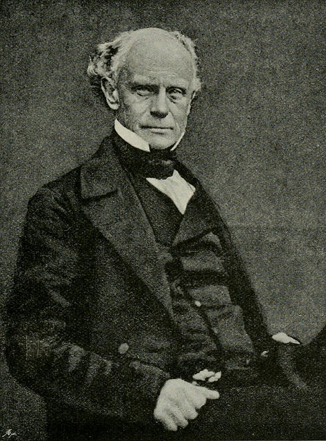 A black-and-white photograph of a white man in his 50s or 60s with receding white hair and a neutral expression.  He is seated and wearing a dark suit.