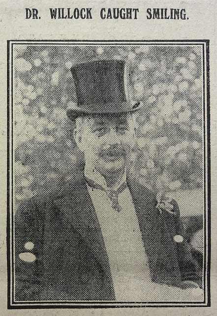 "A black-and-white photo of a white man with a moustache, wearing a top hat and a dark jacket with what looks like a flower in a buttonhole.  He is looking towards the camera and possibly smiling (the caption reads: ""Dr. Willock caught smiling."")"
