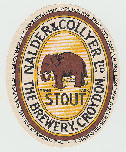 "An oval label with a dark brownish-red elephant in the centre, the words ""Trade Mark"" and ""Stout"" beneath, and ""Nalder & Collyer Ltd / The Brewery, Croydon"" winding around it.  At the very edge of the label are more winding words: ""The company's bottles are vessels to carry beer - not measures - but care is taken that they contain not less than their reputed quantity."""