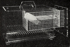 A black-and-white photo of a clear plastic box with a pull-out section studded with airholes.  Some sort of tube, possibly a drinking bottle, is inside, but the details are unclear.