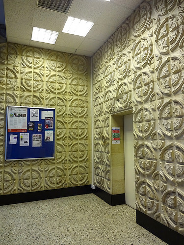 The corner of a hallway, with a lift and noticeboard. The walls are covered with ornate quartered-circle mouldings.