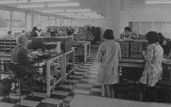 A black-and-white photo of the interior of a low-ceilinged office lit both by daylight and by fluorescent tube lighting.  The floor is dark and light tiles, and the room is filled with long tables with pigeonholes on top.  Several people wearing dresses or skirts are standing or sitting at the tables.