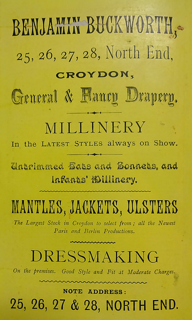 "An advert in a variety of fonts, printed in black on shiny yellow paper, headed ""Benjamin Buckworth, 25, 26, 27, 28, North End, Croydon, General & Fancy Drapery.""  Also advertised are millinery, untrimmed hats and bonnets, mantles, jackets, and ulsters, as well as ""Dressmaking On the premises""."