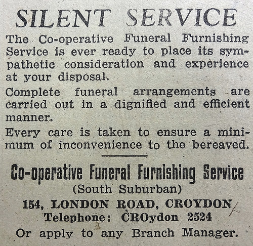 "Monochrome text-only advert headed ""Silent Service"", stating that ""Complete funeral arrangements are carried out in a dignified and efficient manner"" and ""Every care is taken to ensure a minimum of inconvenience to the bereaved.""  At the bottom is the address of the ""Co-operative Funeral Furnishing Service (South Suburban)"" at 154 London Road, Croydon."