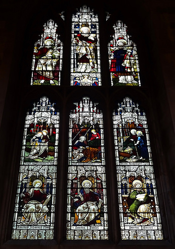A stained-glass window with nine panels showing various saints.