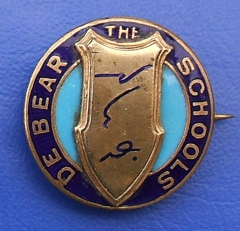 "A round metal/enamel badge with the end of its pin just visible sticking out at the right-hand side.  An elongated bronze shield is in the middle, with three shorthand symbols on it, and ""The De Bear Schools"" is printed in capitals around the edge."