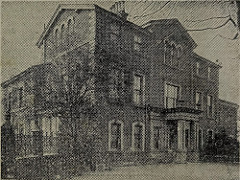 A black-and-white photo of a three-storey house with pillars at the entrance and a wall running away from it on one side.  The photo is taken from a newspaper so is somewhat grainy.
