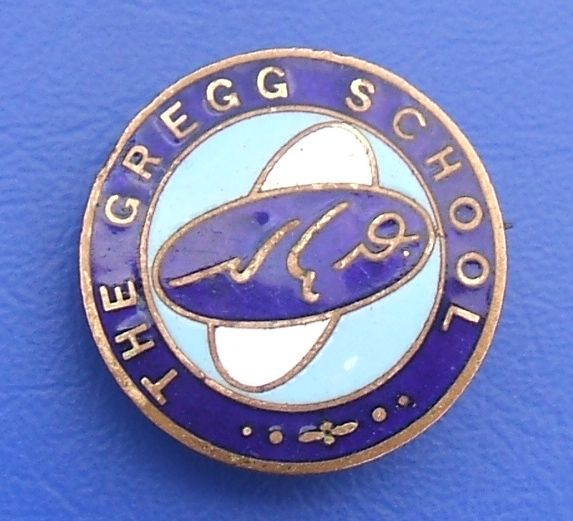 "A similar badge but with no visible pin and what looks like a stylised aeroplace instead of the shield; the same shorthand symbols appear, but the wording this time reads ""The Gregg School""."