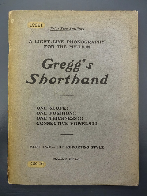 "The cover of a small, thin pamphlet.  It appears to have once been blue, but now has yellowing around the edges, and reads: ""Price Two Shillings / A Light-Line Phonography for the Million / Gregg's Shorthand / One Slope!  One Position!! One Thickness!!! Connective Vowels!!!! / Part Two — The Reporting Style / Revised Edition""."
