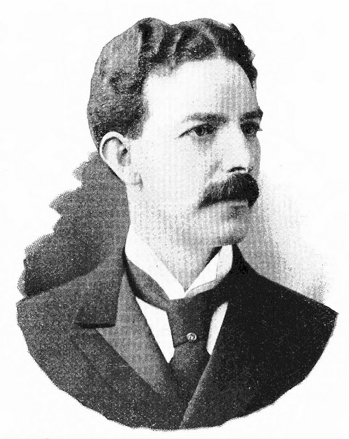 Black-and-white photo of a youngish white man with short, dark, wavy hair and a substantial moustache, looking off towards the right of the image.  He is wearing a white shirt, dark suit jacket, and dark tie.
